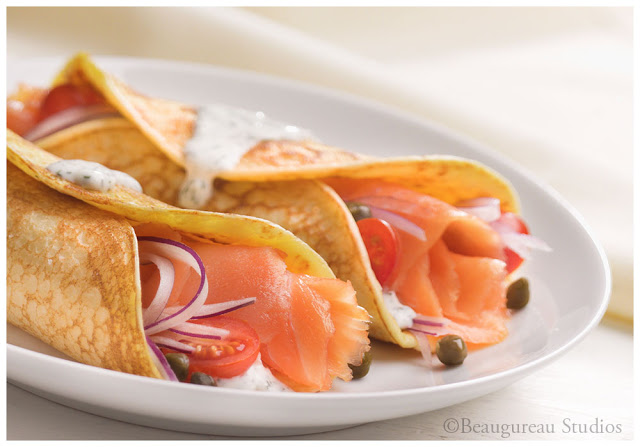 Fresh salmon cut and rolled into crepes, served with cherry tomatoes and onion