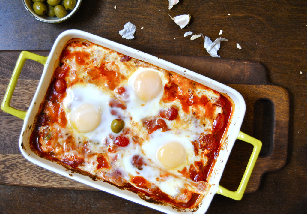 Baked feta with olive, tomatoes, and eggs