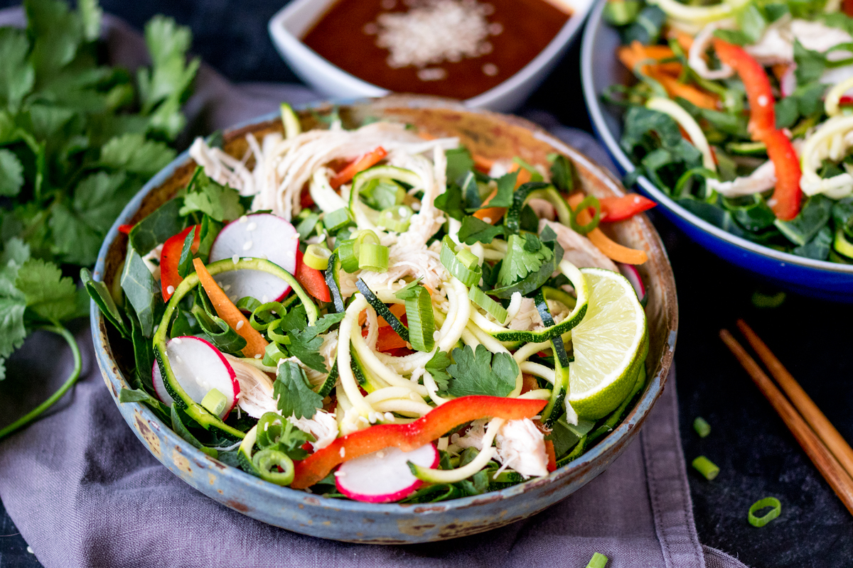 Thai chicken zoodle bowl with a delicious nutty dressing.