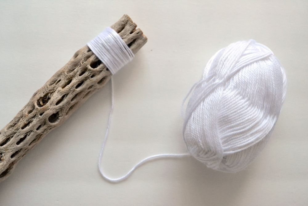 Make a driftwood wall hanger start with white yarn