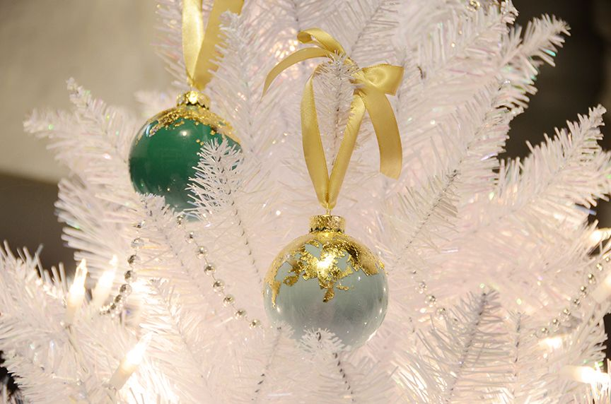 Gold leaf holiday ornaments hanging on tree