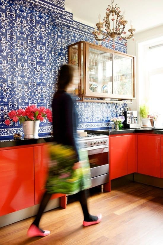 Blue patterned walls red kitchen