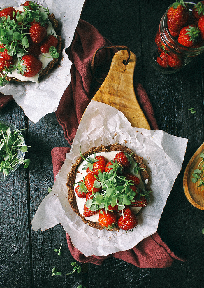 Mini strawberry chocolate tarts with goat cheese and basil microgreens