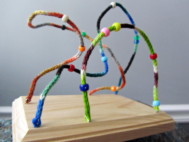 Knitted wire toy with sliding beads