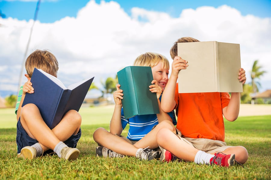 Group of happy kids reading books outside, friendship and learni