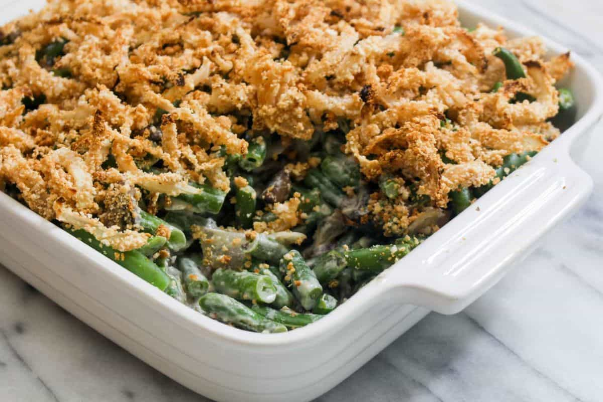 Healthy green bean casserole with homemade crispy onions ceramic bowl