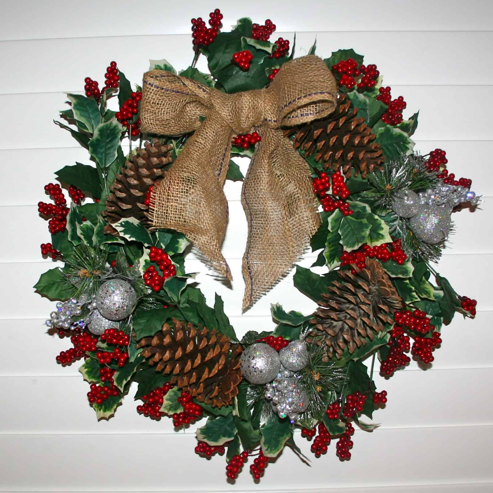 Faux holly leaves and pine cones with a burlap bow