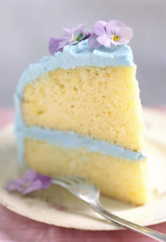 Homemade fluffy vanilla cake with edible flower garnish