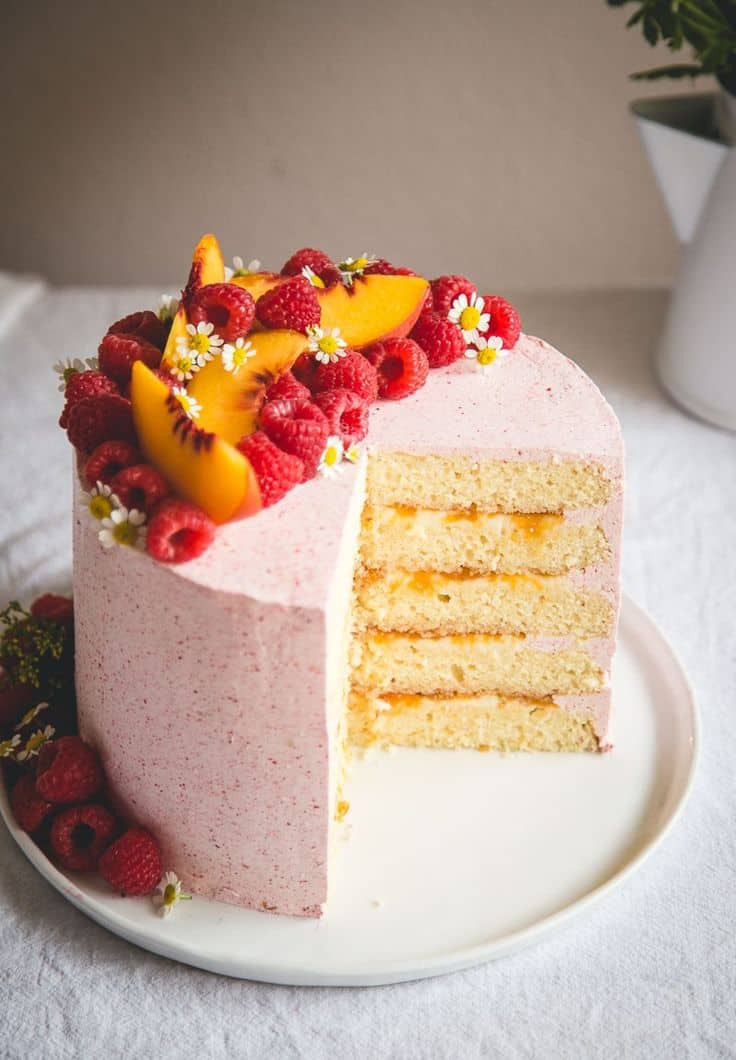 Almond cream cake with peach, mascarpone filling, and raspberry butter cream