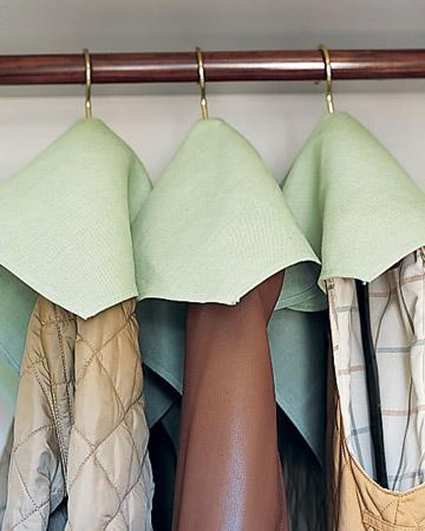Repurpose cloth napkins to keep dust from falling on stored winter coats
