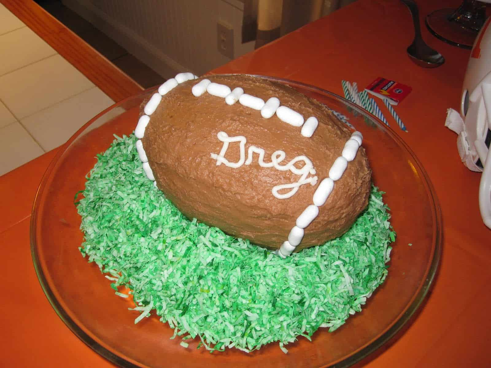 Football cake on dyed shredded coconut grass