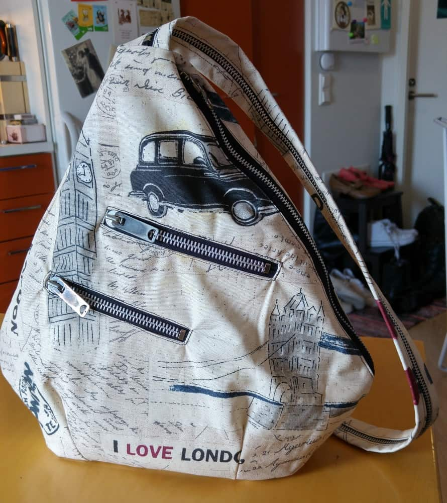Sling backpack with angled pockets