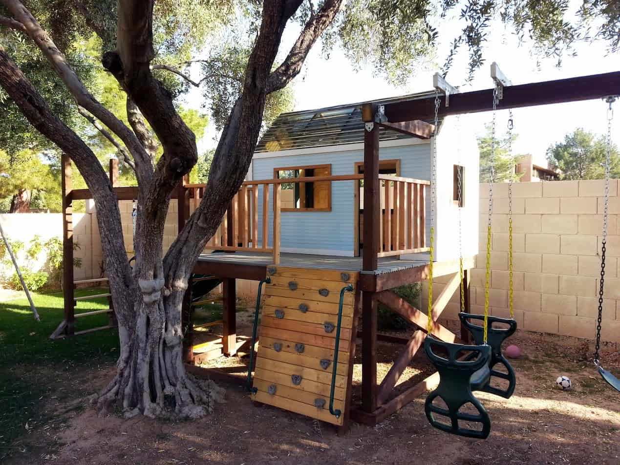 Deck style treehouse with a swing set