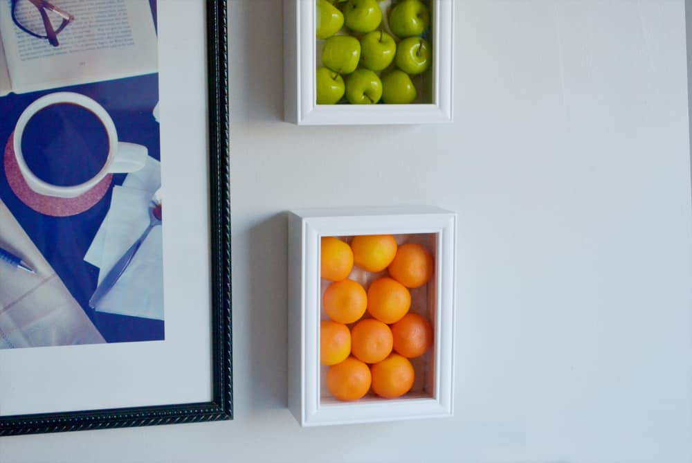 Fake fruits framed on wall