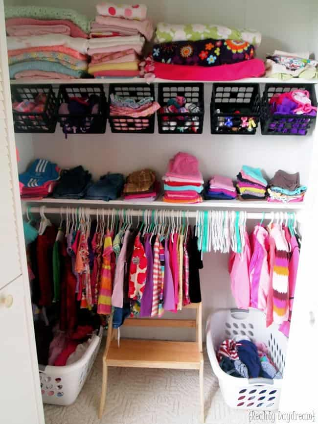 Double height kids' closet with hanging storage baskets