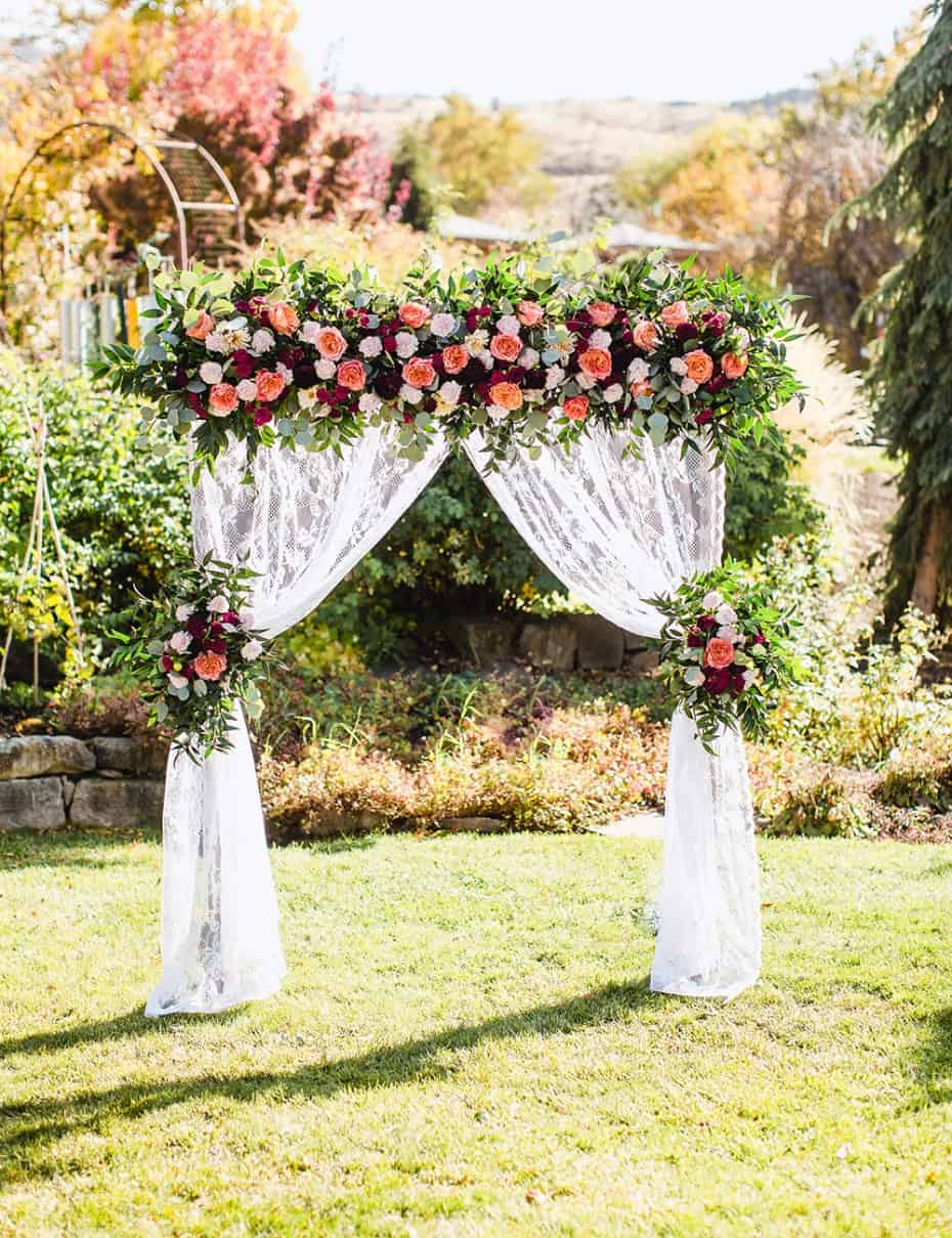 Lace curtain and floral bouquet wedding arbor