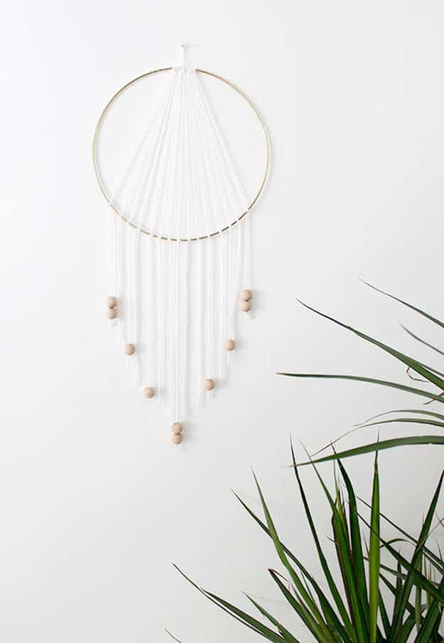 Modern metallic, wood, and white dreamcatcher inspired wall hanging