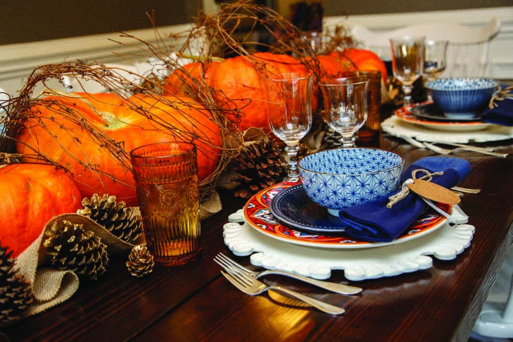 Branch wrapped pumpkins and pinecones thanksgiving table