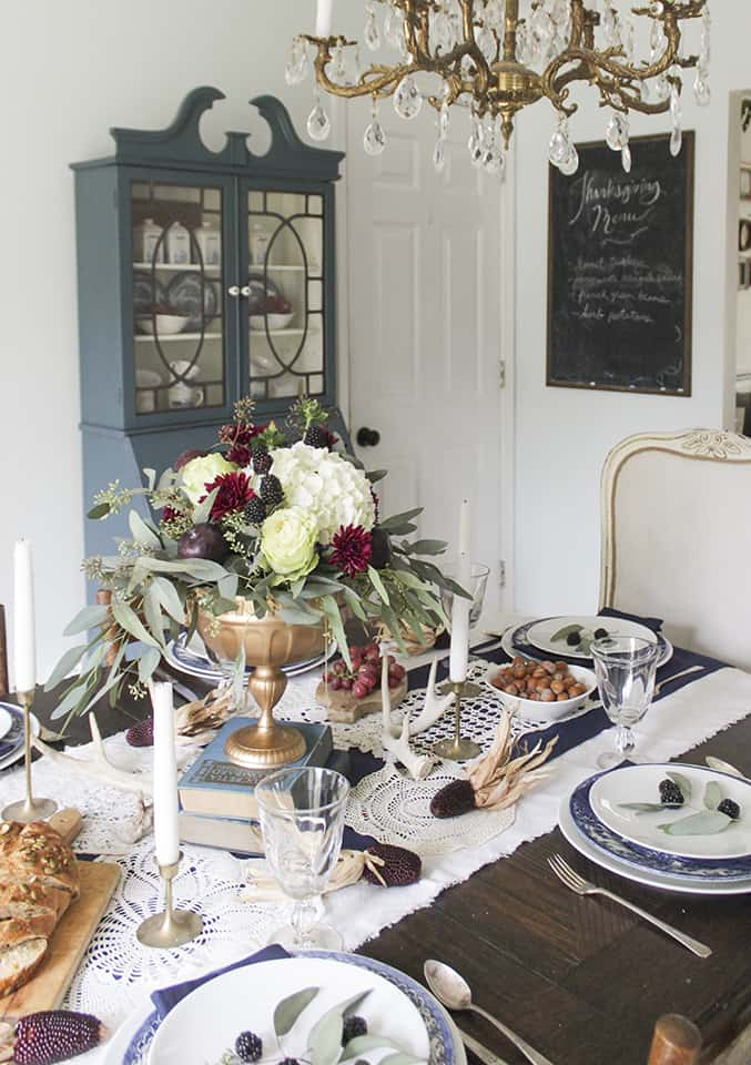 Raised book and vase centrepiece in a burgundy, navy, and gold tablescape