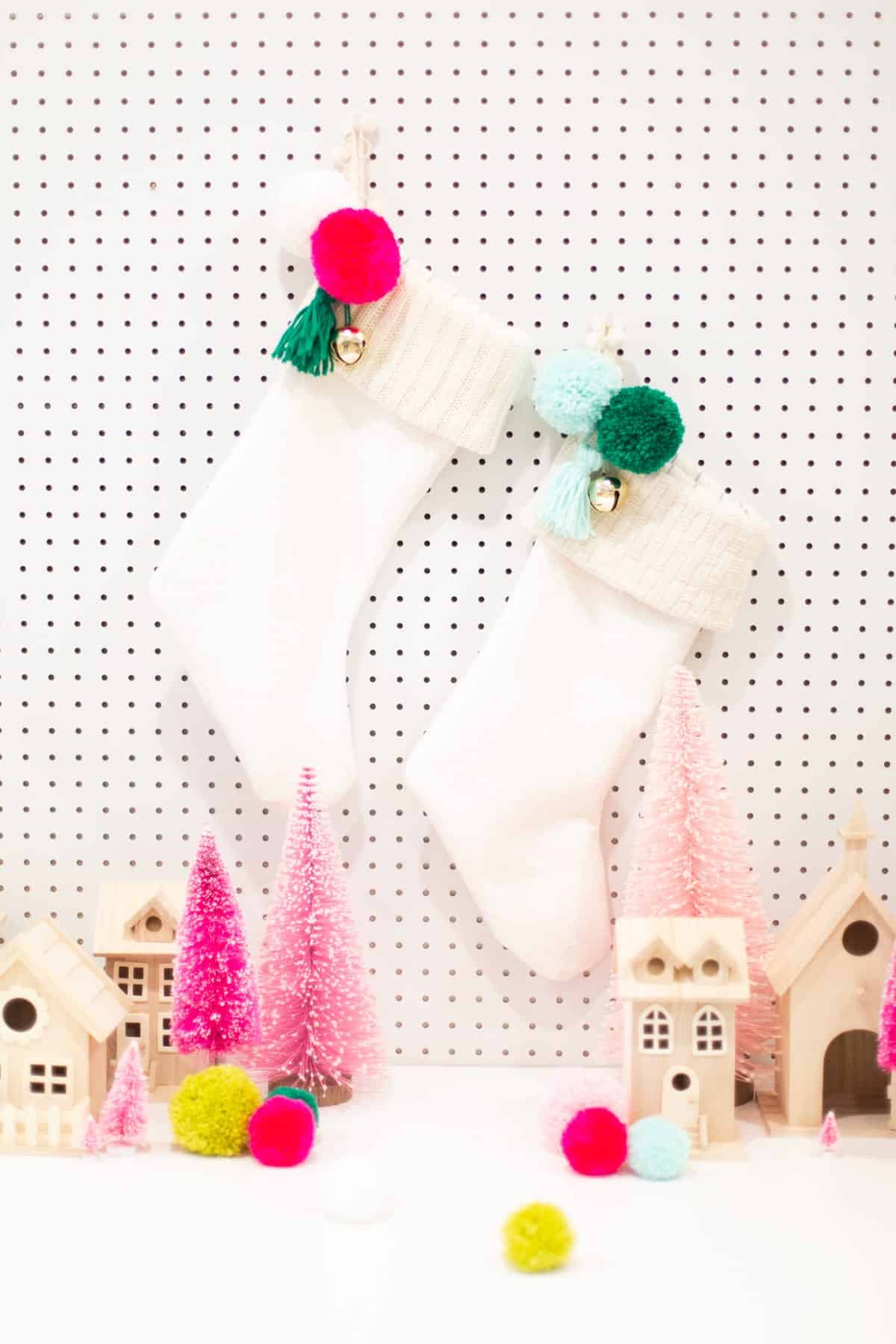 Lined christmas stocking with a knit cuff and trinket with pom poms and bells