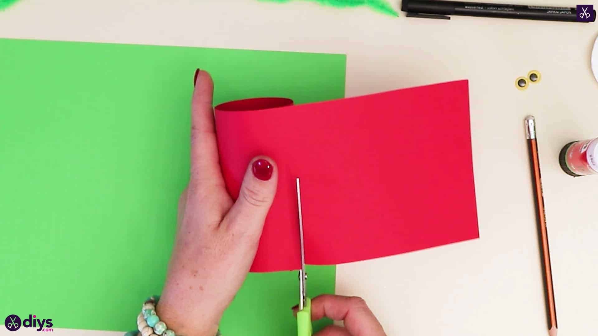 Toilet paper roll grinch cutting red paper