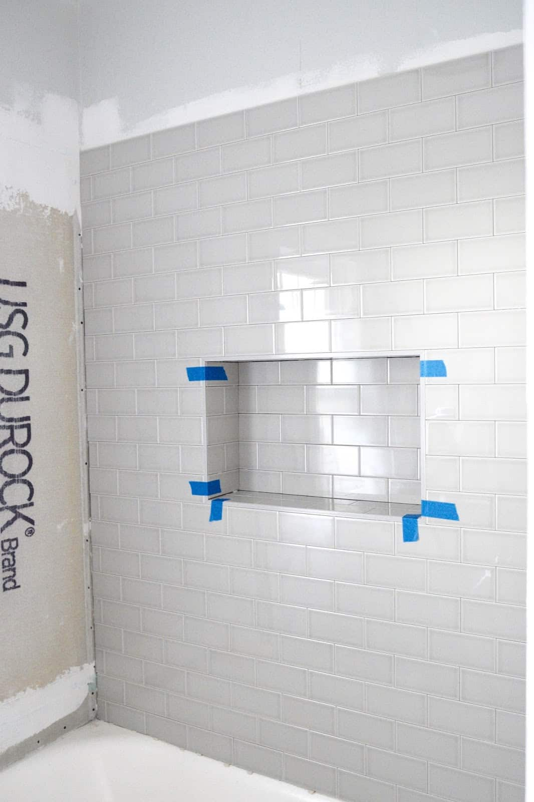 Subway tiling a wall with a shower niche