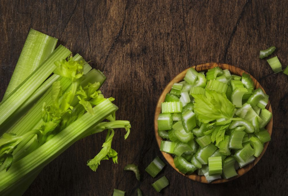 Fresh green celery chopped pieces in bowl, vintage wooden background, top view, copy space