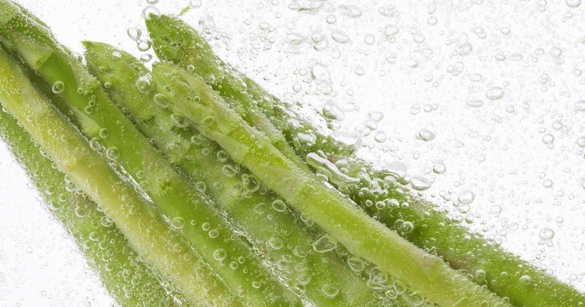 Asparagus being submerged into water