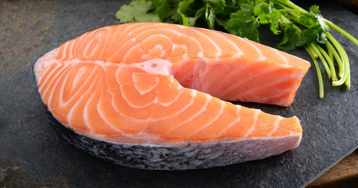 A salmon steak on a ceramic plate with coriander by its side