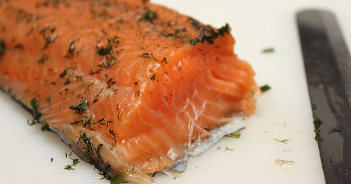 A salmon side with various herbs on its flesh on top of a white chopping board