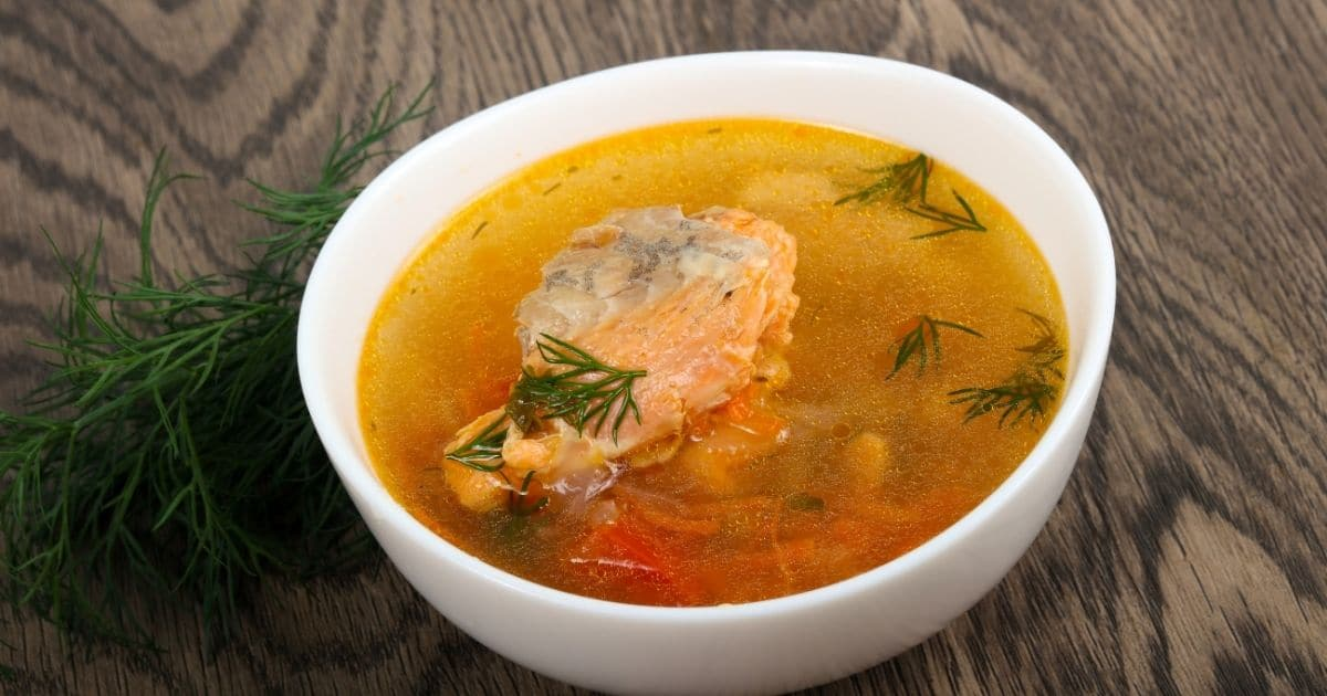 Salmon soup garnished with thyme, on a white bowl on top of a wooden table