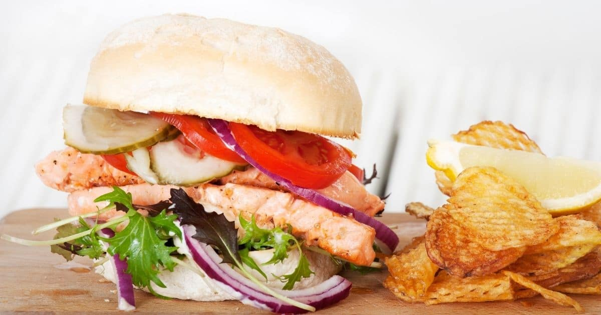 Burger buns filled with a couple of salmon fillets, tomatoes, gherkins, red onion, and rocket. The burger is accompanied with fries, lemon and it is served on a wooden board