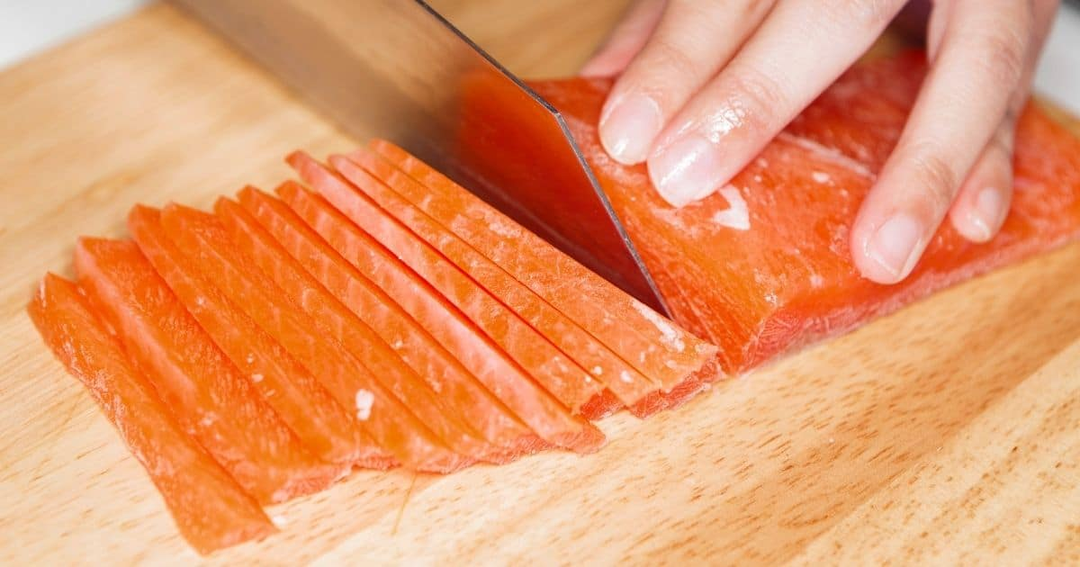 A pair of hands cutting a large piece of salmon