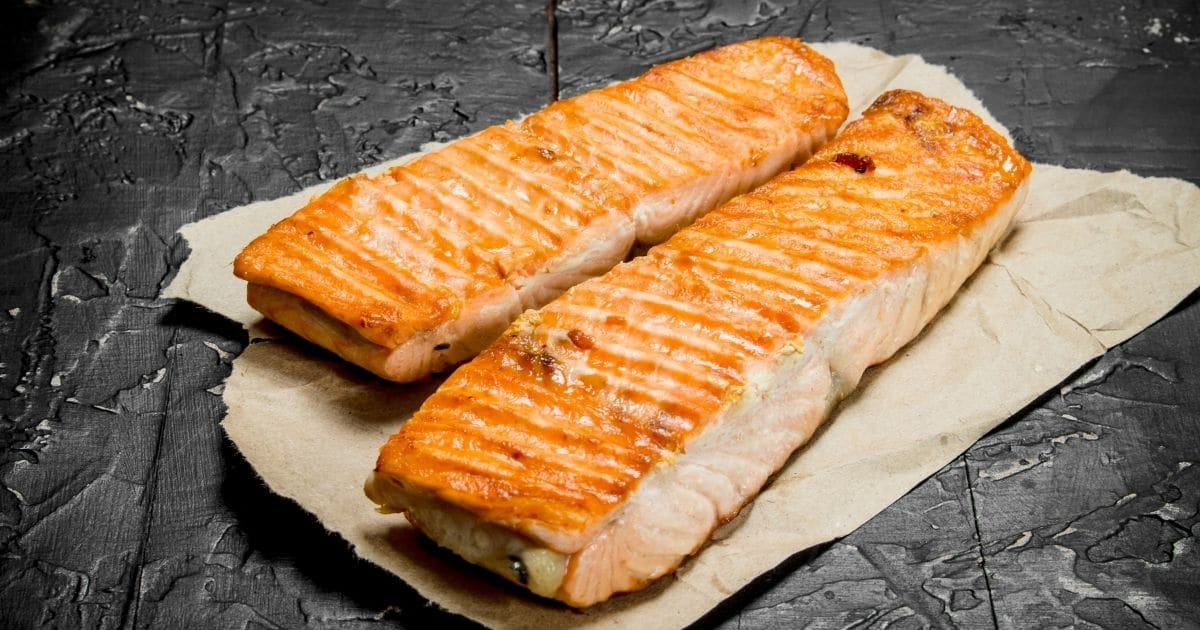 Two individual pieces of salmon on top of parchment paper