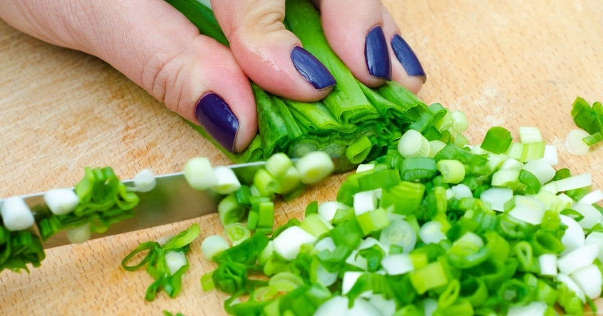 Green onions being chopped on a wooden chop board