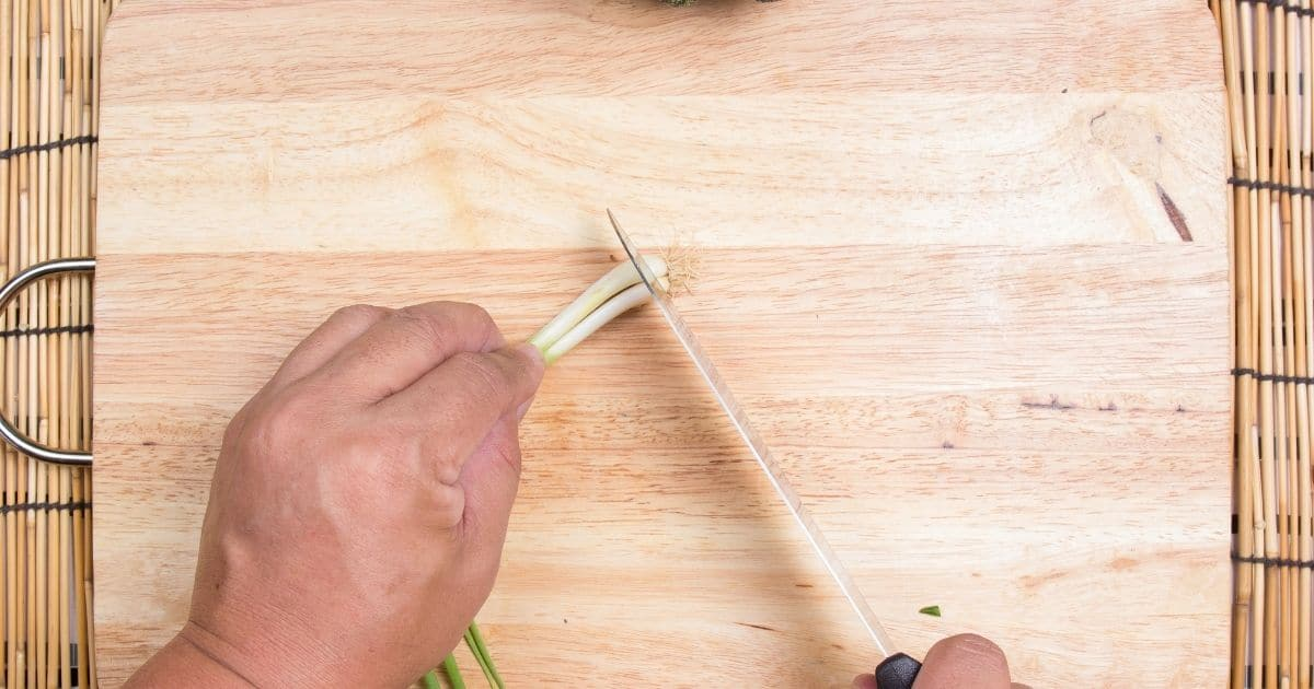 The roots of green onions being cut off on a chopping board
