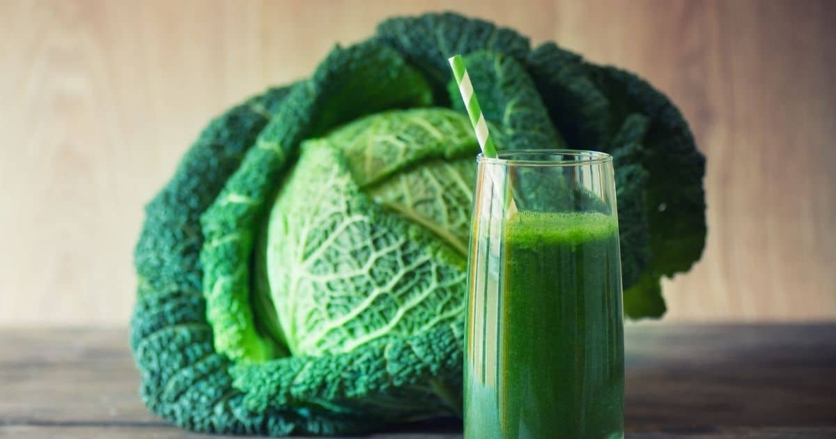 A crystal glass of green smoothie next to a whole cabbage