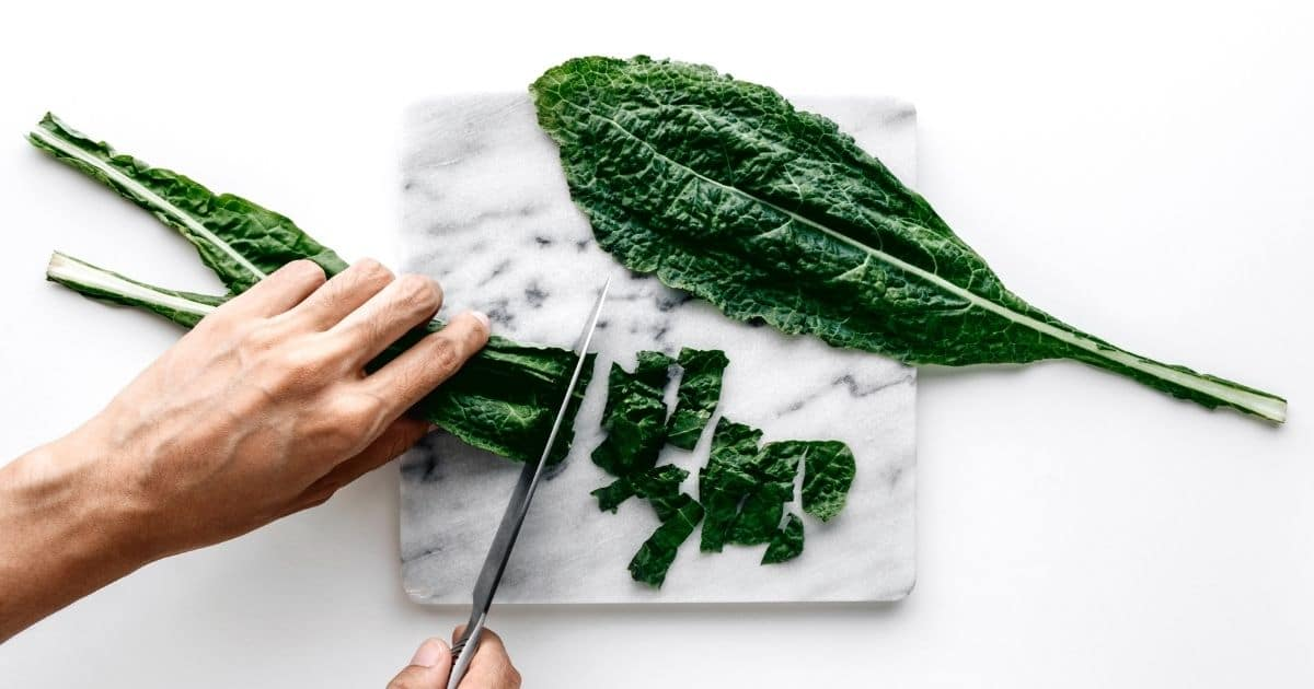 Kale leaves being chopped on a withe and grey chopping board