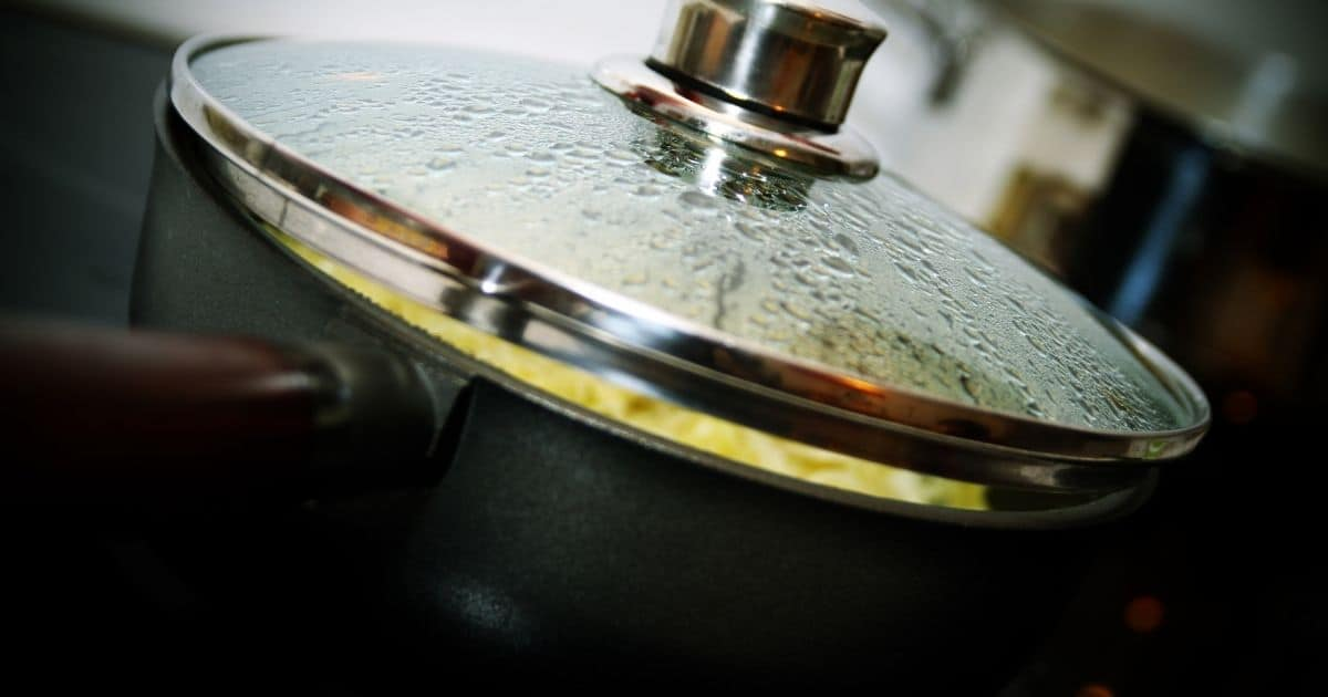 A metal deep pan with steam inside the lead