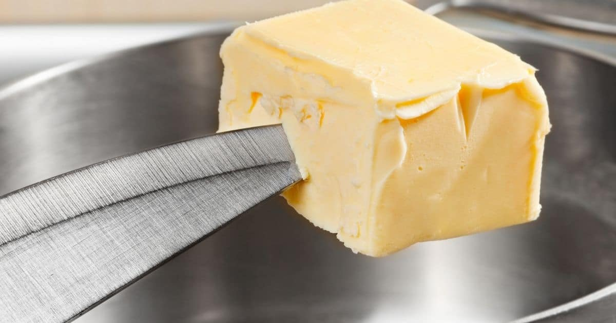 A large block of butter, at the end of the knifes tip, about to be placed inside a metal saucepan
