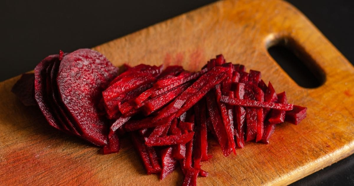A beetroot being cut into ¼ inch thick pieces