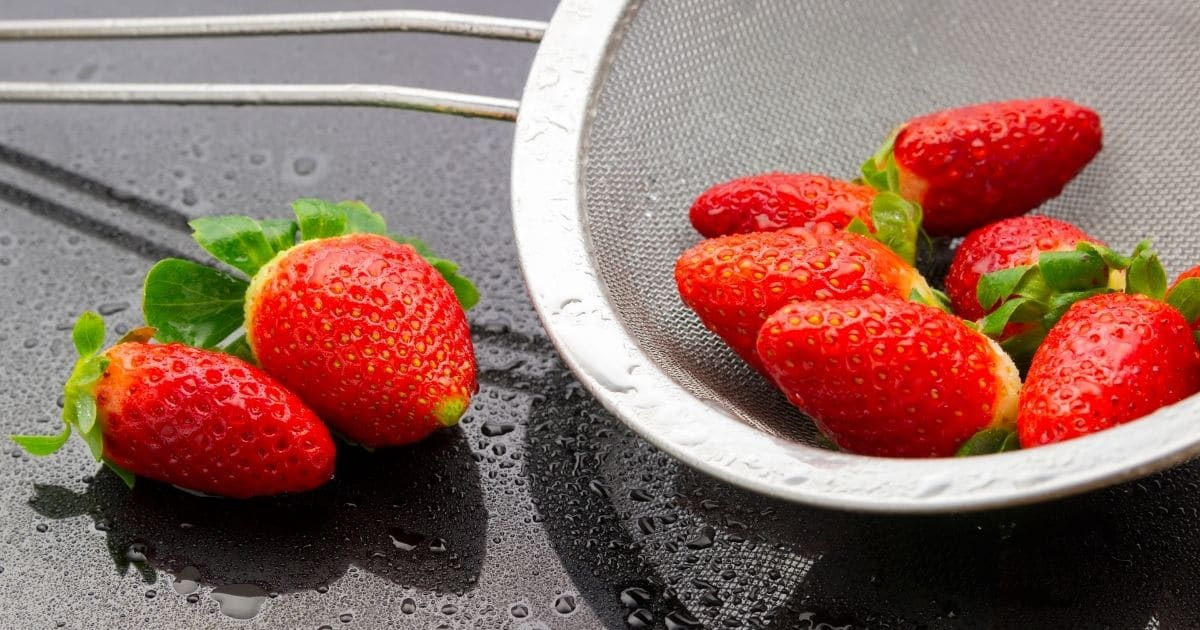 Strawberries being dried in a strainer