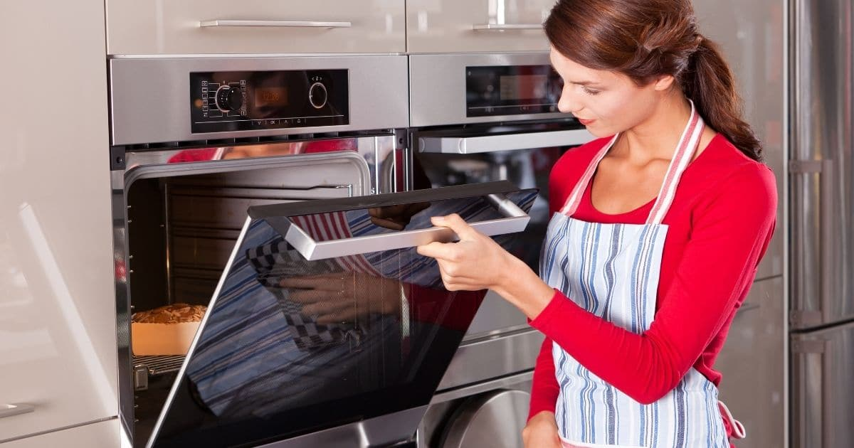 A lady placing the sweet potatoes in the oven